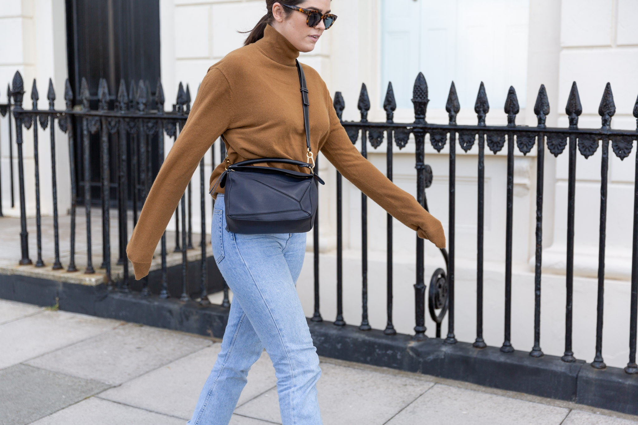 A photo of Anna walking down the street in a brown turtleneck, jeans and her Loewe bag.