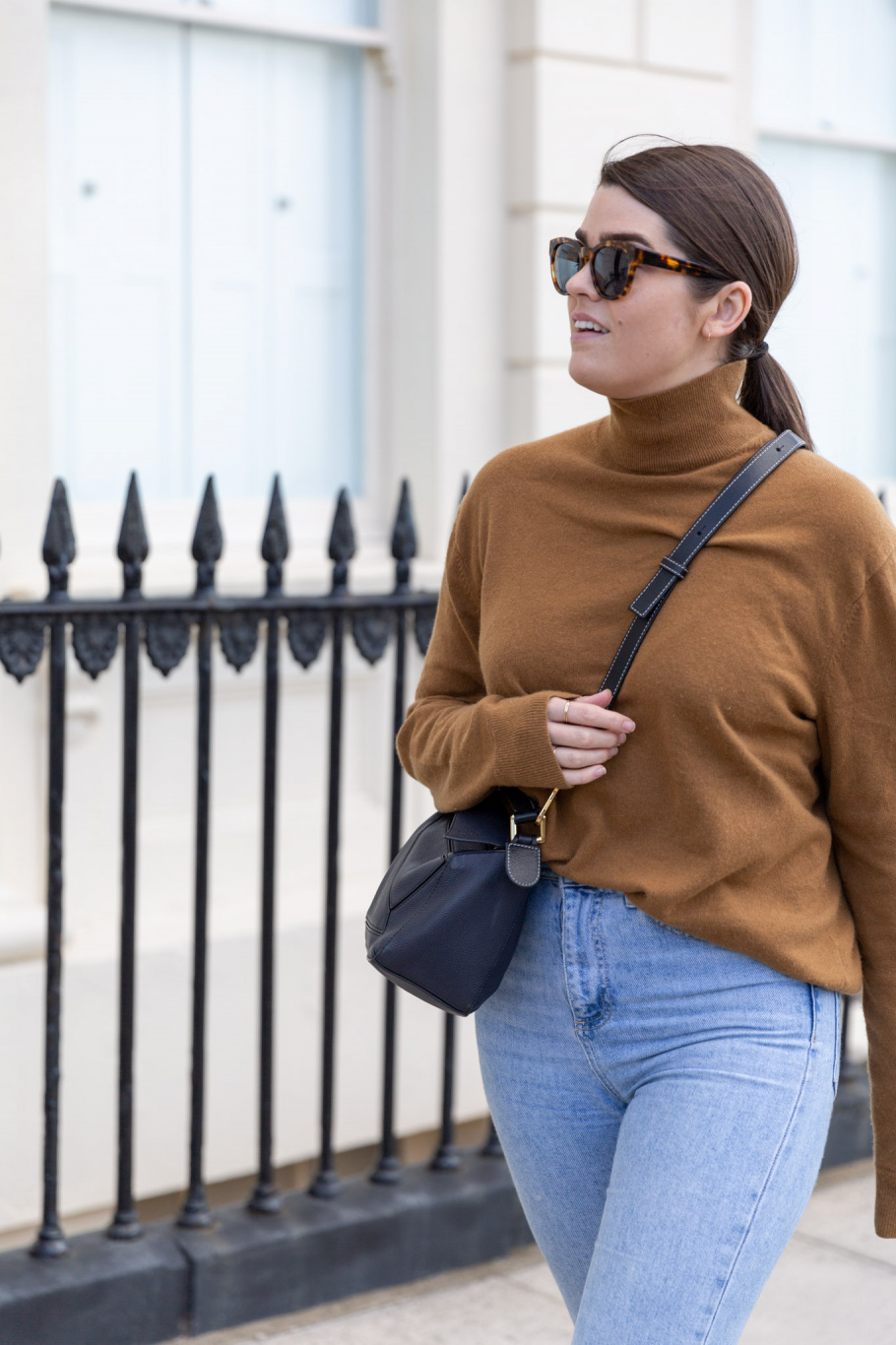 A photo of Anna walking down the road in her knitwear.