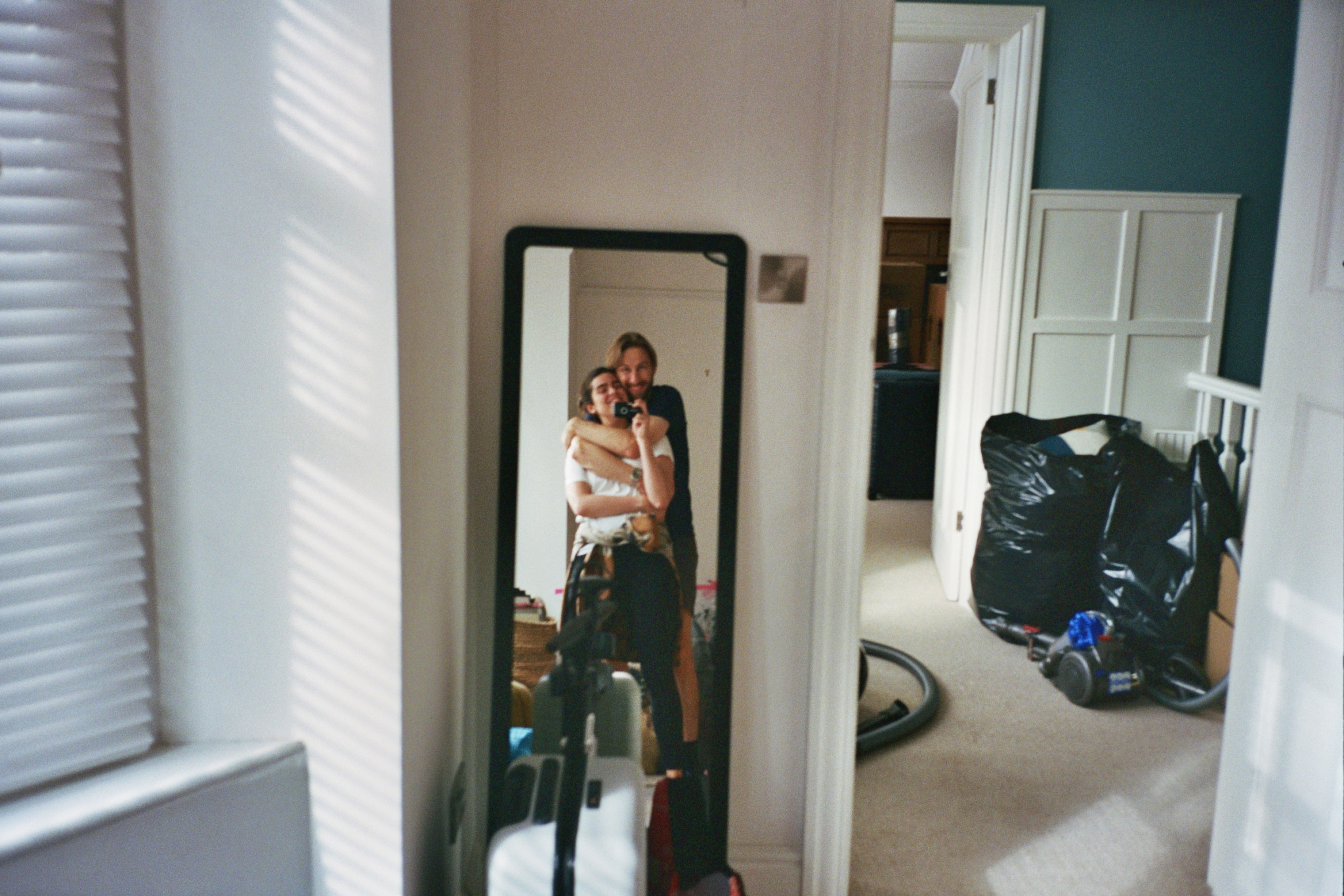 A picture of Anna and Mark in front of their mirror in the midst of packing