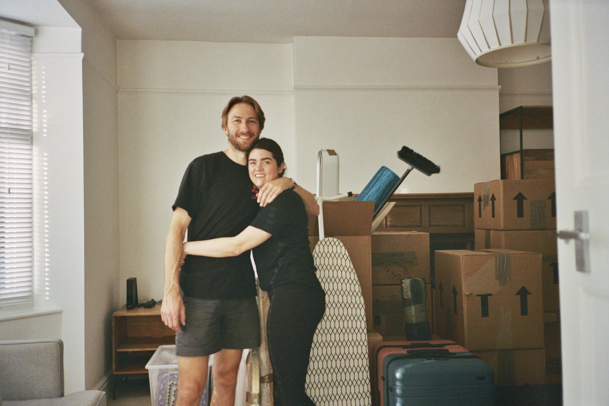 A photo of Anna and Mark in their front room that's full of moving boxes